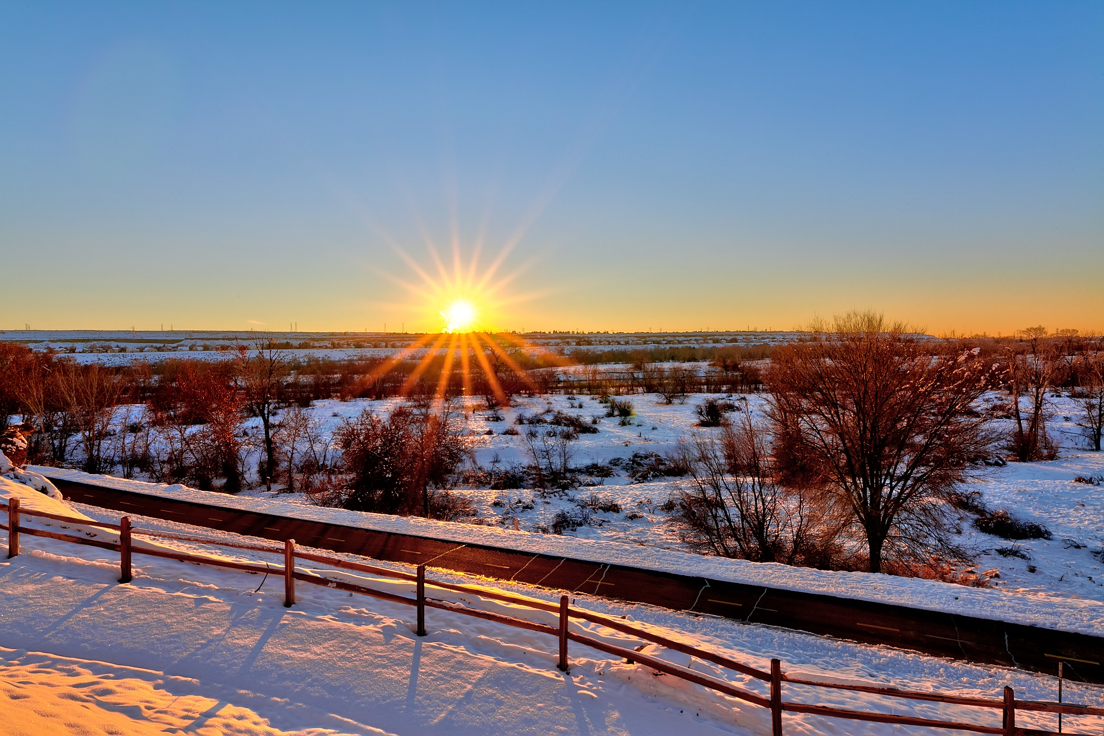 Photo of a peaceful valley covered in snow, with the sun setting in the distance.