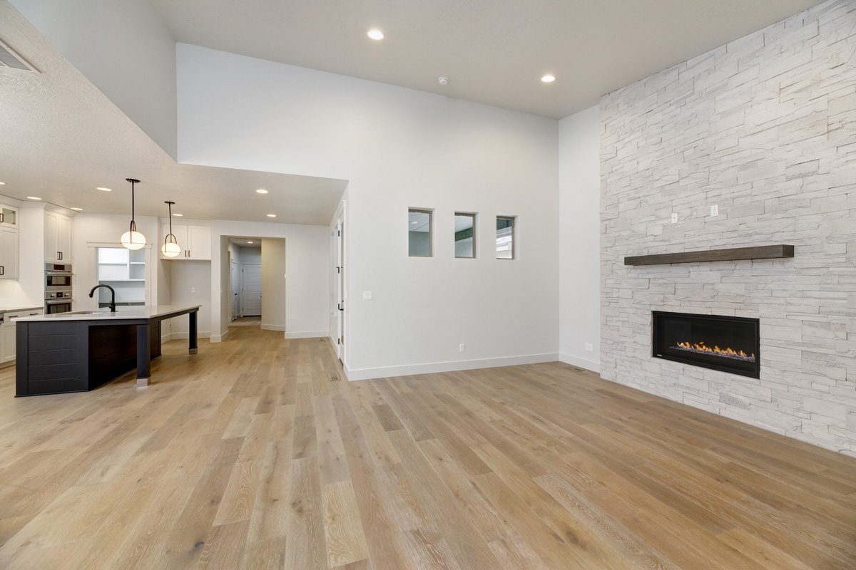 Open-concept living room in The Winslow, with light and bright walls, stone fireplace, and nearby gourmet kitchen.