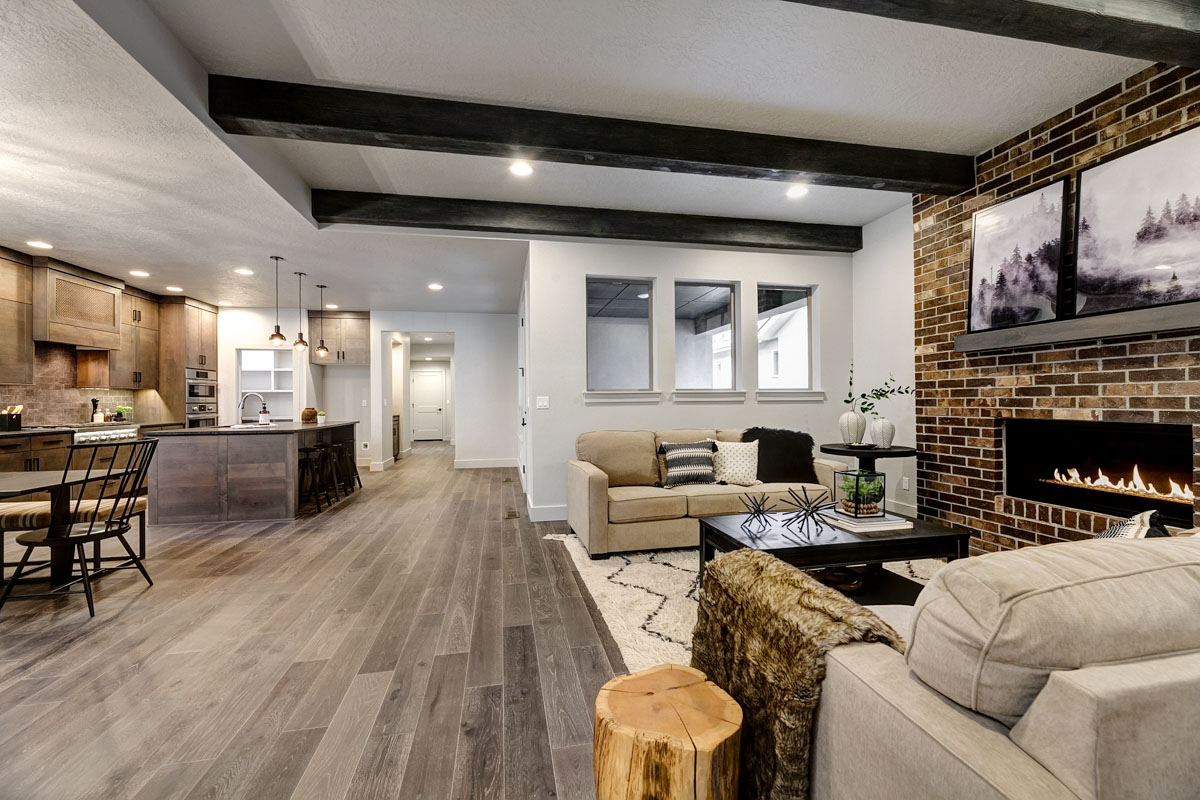 Photo of the open-concept living room and kitchen with a brick fireplace, exposed wood beam, and a gourmet kitchen.